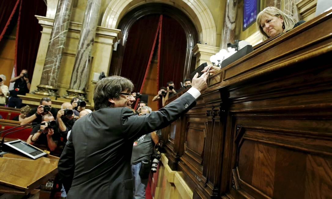 Presidente catalão, Carles Piugdemont, deposita seu voto durante sessão do Parlamento; sob ameaça de até 30 anos de prisão, líder comanda o movimento separatista Foto: Manu Fernandez / AP