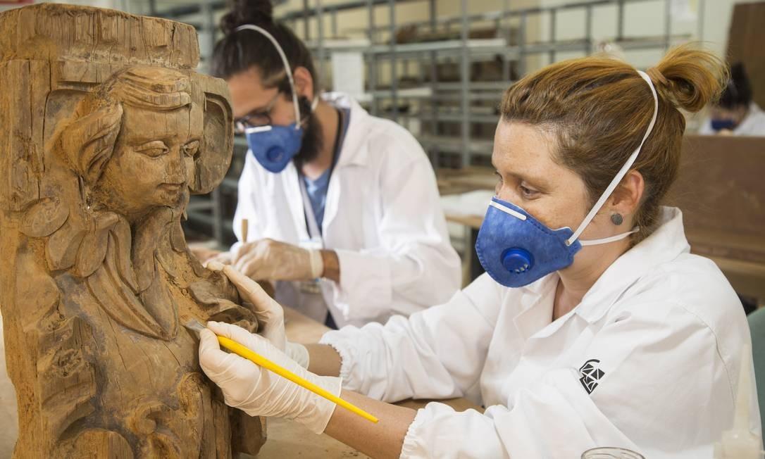 Os restauradores Carla Sousa e Elton Hipolito trabalham no restauro de peças que pertenciam a igrejas destruídas pela lama Ana Branco / Agência O Globo