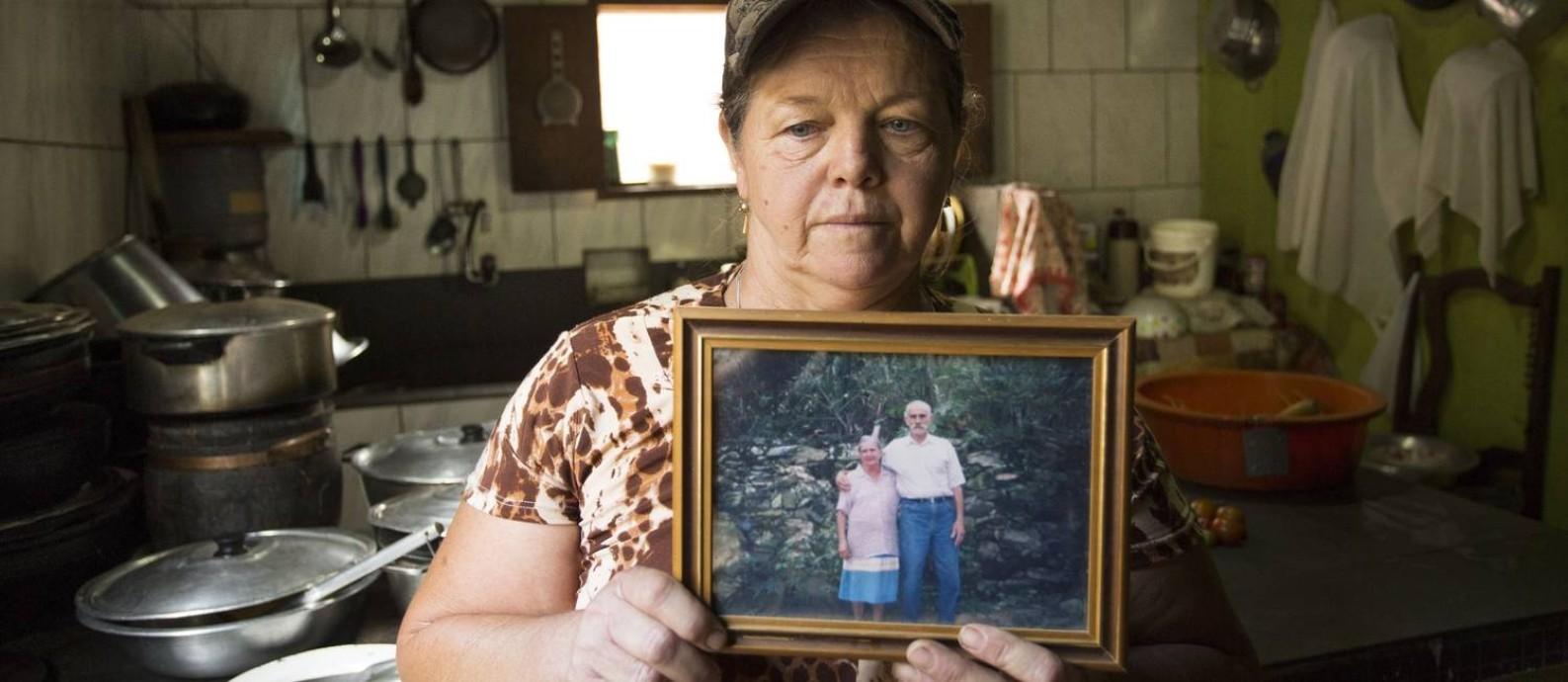 """Valdalice Arcanjo mostra foto da sogra Terezinha, que morreu em agosto à espera de recuperar o que construíra com o marido por 60 anos: """"A lama arrasou com a vida da nossa família, mudou tudo, acabou a alegria"""" Foto: Ana Branco / Agência O Globo"""