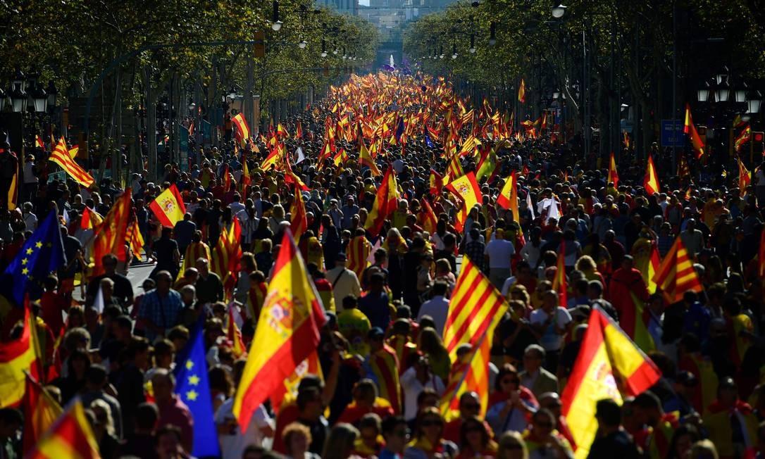 Pessoas carregam bandeiras espanholas, catalãs e da União Europeia durante uma manifestação a favor da unidade da Espanha em Barcelona. Há dois dias, governo da Catalunha declarou independência, levando a região e o país a uma crise política Foto: PIERRE-PHILIPPE MARCOU / AFP