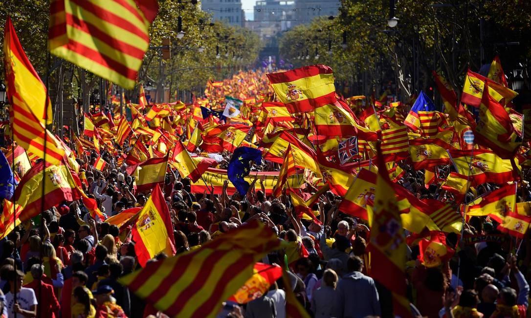 Manifestantes balançam bandeiras espanholas e catalãs durante marcha a favor da unidade da Espanha em Barcelona. Mais de um milhão de pessoas se reuniram no centro da cidade para um grande protesto pacífico após Madri destituir o governo regional, em resposta à declaração unilateral de independência Foto: PIERRE-PHILIPPE MARCOU / AFP