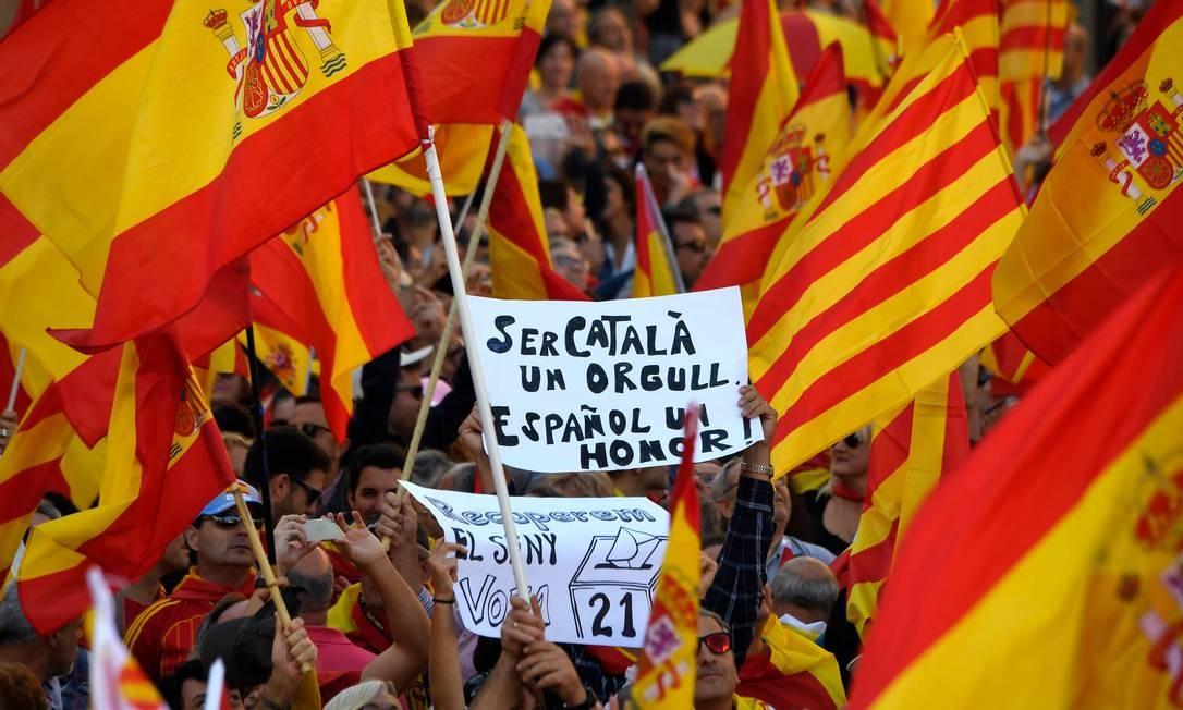 """Manifestante segura cartaz """"Ser catalão é um orgulho, ser espanhol é uma honra"""" durante marcha pró-Espanha em Barcelona. Inquietos após a declaração unilateral de independência, catalães contrários à secessão saem às ruas mostrando a divisão na região Foto: LLUIS GENE / AFP"""