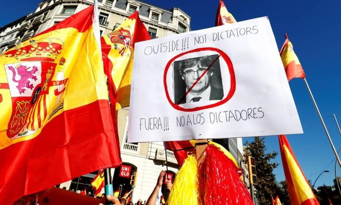 """Cartaz com imagem de líder catalão, Carles Puigdemont, diz """"Fora! Não aos ditadores"""" em manifestação a favor da unidade da Espanha. Considerada uma ofensa pelos separatistas, a intervenção de Madri na região é vista com certo alívio por cerca de metade dos 7,5 milhões de habitantes da Catalunha que, após anos eclipsados pelas mobilizações independentistas, aumentaram seus protestos Foto: YVES HERMAN / REUTERS"""
