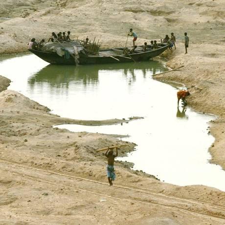 Crianças indianas brincam em barco preso em rio seco ao Oeste de Calcutá Foto: Jayanta Shaw / Reuters/4-6-2003