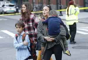 Atônitos, pais levam crianças após ataque em Nova York Foto: SHANNON STAPLETON / REUTERS