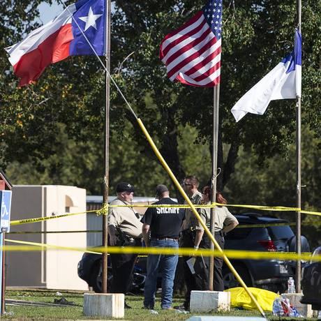 Policiais conversam próximo a um corpo coberto no local do ataque a tiros na Primeira Igreja Batista em Sutherland Springs, no Texas, on Sunday, Nov. 5, 2017 Foto: Nick Wagner / AP