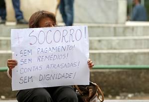 Servidora do estado ergue cartaz em protesto contra salários atrasados Foto: Márcio Alves 13-06-2017 / Agência O Globo