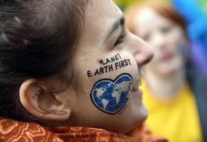 """Manifestante pinta o slogan """"Primeiro o planeta Terra"""" em protesto do Greenpeace em Bonn Foto: HENNING KAISER / AFP"""
