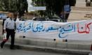 Homem passa por cartaz em bairro sunita de Beirute dizendo 'Todos somos Saad al-Hariri', em alusão ao premier que renunciou Foto: MOHAMED AZAKIR / REUTERS