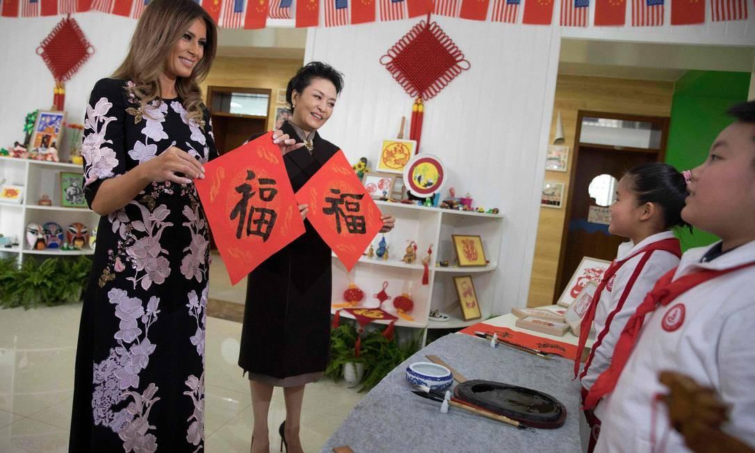 As duas primeiras-damas foram presenteadas com trabalhos dos alunos com o símbolo chines da fortuna NG HAN GUAN / AFP
