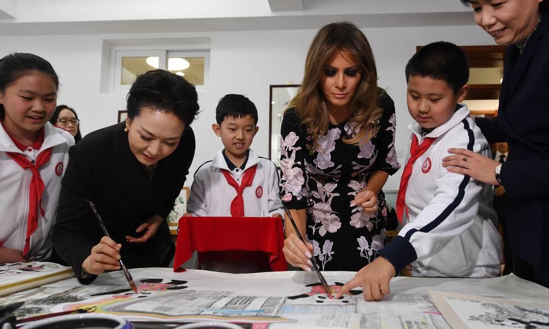 E testou suas habilidades na delicada arte da caligrafia chinesa, sob os olhos atentos dos alunos da escola GREG BAKER / AFP