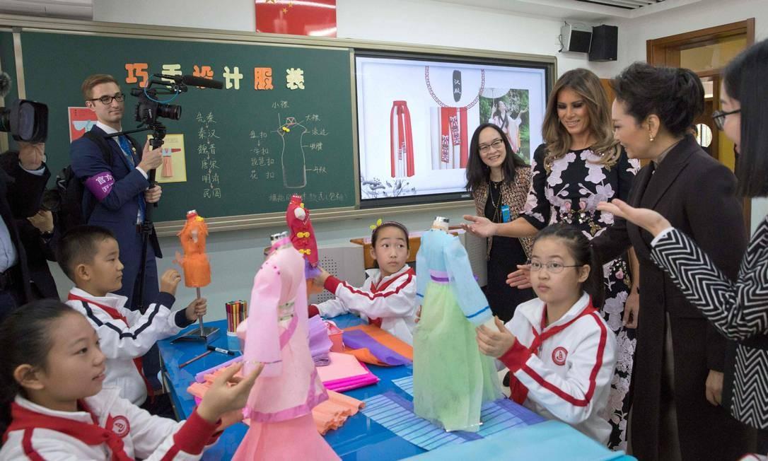Melania Trump e Peng Liyuan observam os alunos durante a aula de moda NG HAN GUAN / AFP