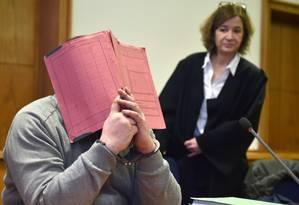Niels Hoegel esconde o rosto durante um julgamento na Corte de Oldenburg em 2015 Foto: CARMEN JASPERSEN/AFP/26-2-2015