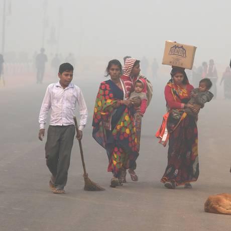 Indianos andam em rua de Nova Délhi: poluição atmosférica está muito acima de nível considerado tolerável Foto: DOMINIQUE FAGET / AFP