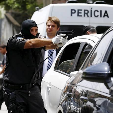 Com o rosto coberto, policial participa da simulação da morte do coronel Luiz Gustavo Teixeira Foto: Pablo Jacob / Agência O Globo