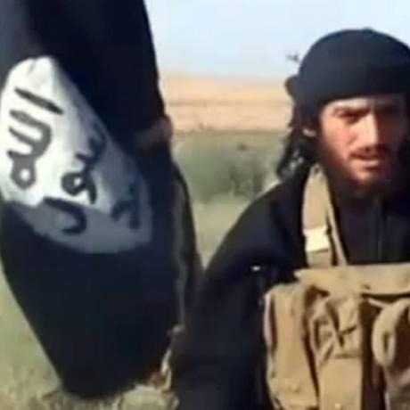 O então porta-voz do Estado Islâmico, Abu Mohammad al-Adnani al-Shami, fala ao lado de uma bandeira islâmica em um local não revelado em julho de 2012. Foto: AFP