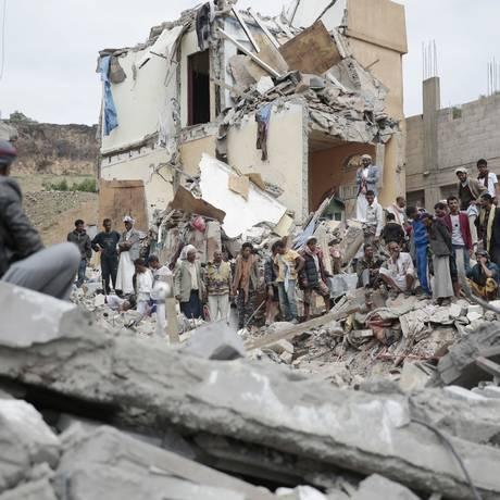 Em foto de agosto, moradores observam casas destruídas por bombrdeios sauditas em Sanaa, capital do Iêmen Foto: Hani Mohammed / AP