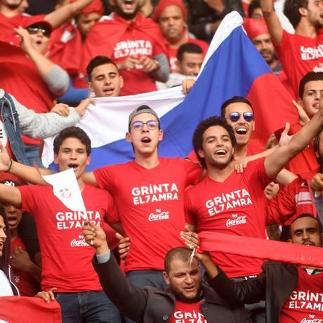 Torcedores tunisianos que lotaram o estádio comemoram com a bandeira da Rússia a classificação para a Copa Foto: FETHI BELAID / AFP