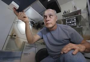 Osmar Alfena mostra o botão do pânico embaixo da mesa de seu escritório: ele tem mais dois dispositivos: um fica numa parede, e o outro é um controle de bolso Foto: Marcio Alves / Agência O Globo