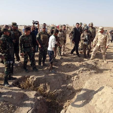 Forças iraquianas examinam local de vala comum onde Estado Islâmico teria enterrado mais de 400 pessoas Foto: AFP/MARWAN IBRAHIM