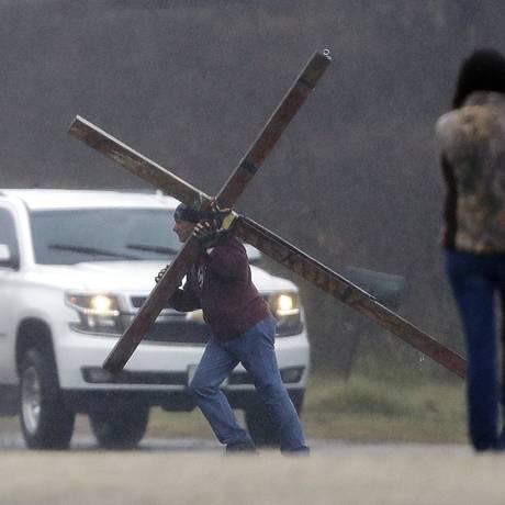 Homem carrega uma cruz nas proximidades da igreja batista onde um massacre ocorreu no último domingo, em Sutherland Springs, no estado americano do Texas. Foto: Eric Gay / AP