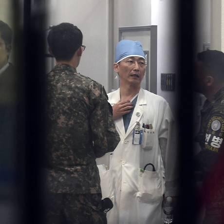 Soldados sul-coreanos conversam com médico enquanto ele se prepara para operar o homem resgatado na fronteira Foto: Lee Jung-son / AP