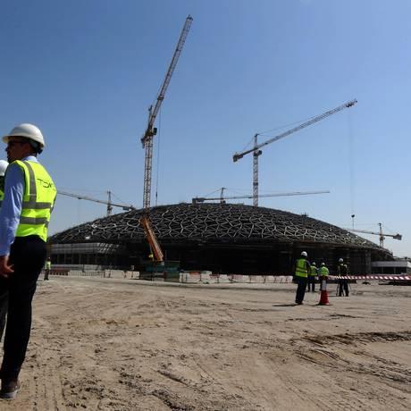 Funcionários trabalham na obra do Louvre de Abu Dhab, que foi inaugurado neste sábado Foto: MARWAN NAAMANI / AFP