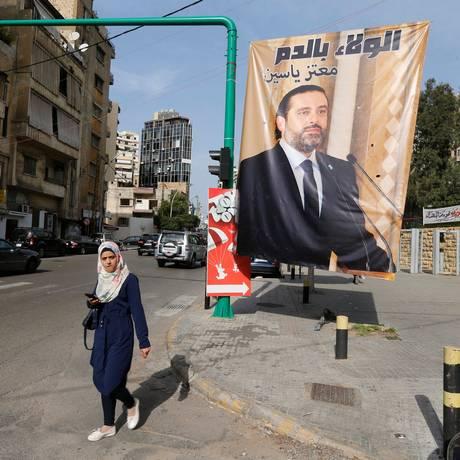 Pedestre passa por pôster de Hariri em Beirute Foto: MOHAMED AZAKIR / REUTERS
