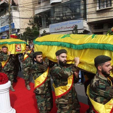 Membros do Hezbollah carregam caixões de combatentes mortos na Síria, durante funeral em Nabatieh, em 8 de novembro Foto: MAHMOUD ZAYYAT / AFP