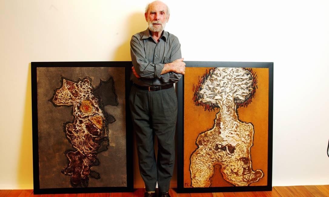 Frans Krajcberg posa entre duas de suas telas em 2005. Engajado em causas naturais, o artista sempre retrata a natureza em seus trabalhos, que já transitaram pela pintura, escultura, gravura e fotografia Foto: Camilla Maia / Divulgação