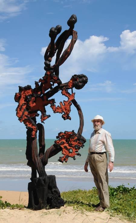 Krajcberg ao lado de uma de suas obras ao ar livre. Ele se tornou famoso por criar esculturas feitas a partir de troncos e raízes de árvores calcinadas pelos incêndios que derrubam densas áreas verdes Foto: Divulgação