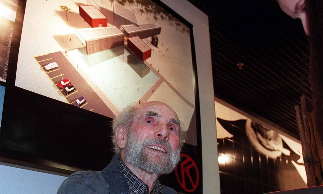O artista posa à frente de uma imagem da construção do Museu Krajcberg. A foto é do ano 2000. Até o fim de sua vida, ele batalhou para conseguir construí-lo. No entanto, Krajcberg reclamava da falta de apoio. Foto: Luiz Carlos Santos / Divulgação