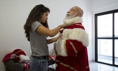 Limachem, com barba real, encarnando o Papai Noel com a ajuda de sua filha Slanny Foto: Leo Martins / Agência O Globo
