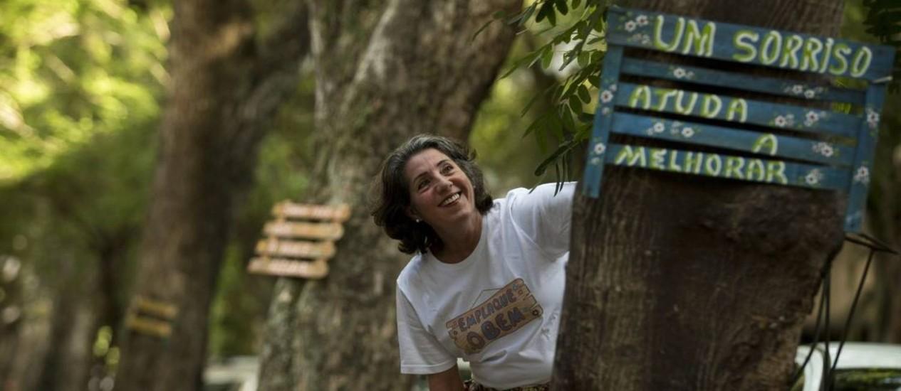 Helen Maria faz placas de madeira com palavras e coloca nas árvores da cidade Foto: Márcia Foletto / Agência O Globo