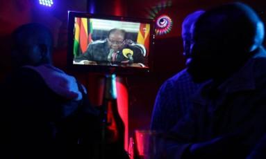 Em Harare, zimbabuanos assistem a pronunciamento do presidente Robert Mugabe dias após intervenção militar Foto: PHILIMON BULAWAYO / REUTERS