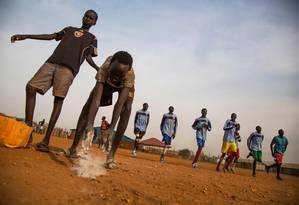 Jovens deslocados preparam quadra para jogar futebol em Juba, capital do Sudão do Sul Foto: ALBERT GONZALEZ FARRAN / AFP
