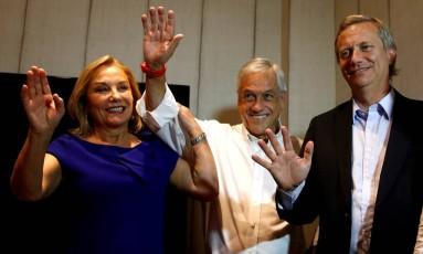 Acompanhado pelo deputado de extrema-direita José Antonio Kast (direita) e a mulher, Cecilia, Piñera saúda apoiadores em Santiago Foto: STRINGER / REUTERS