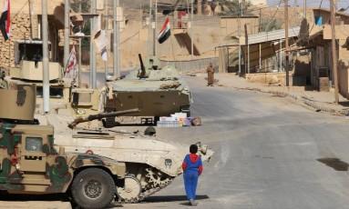 Menino caminha ao lado de forças iraquianas em Rawa Foto: SULEIMAN AL-ANBARI 18-11-2017 / AFP