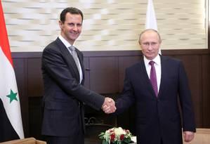 O presidente russo, Vladimir Putin, aperta a mão de seu homólogo, Bashar al-Assad, durante um encontro em Sochi, no Sudoeste da Rússia Foto: MIKHAIL KLIMENTYEV / AFP