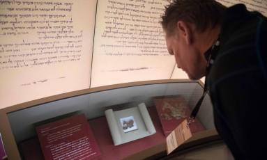 Visitante observa fragmento dos pergaminhos do Mar Morto no Museu da Bíblia, em Washington Foto: SAUL LOEB / AFP