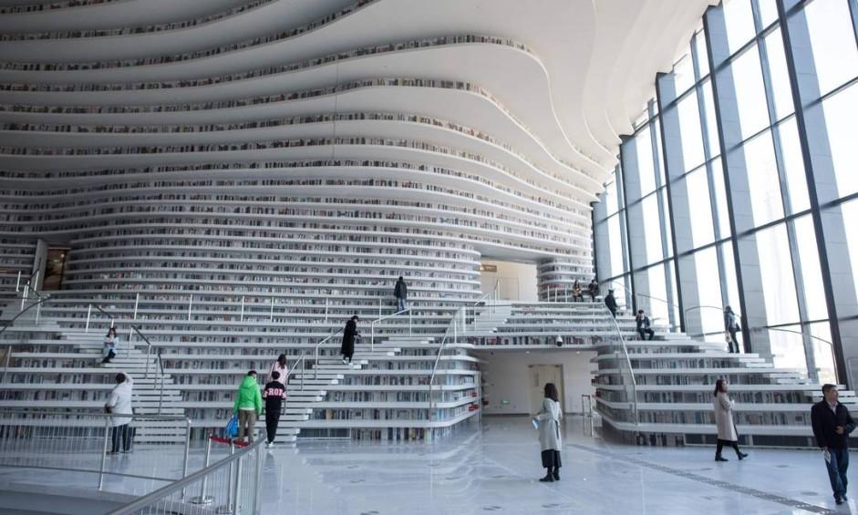 Desde sua inauguração, em outubro, a biblioteca Binhai, em Tianjin, na China, vem encantando os frequentadores com suas estantes brancas e onduladas, que vão do chão ao teto. Foto: FRED DUFOUR / AFP