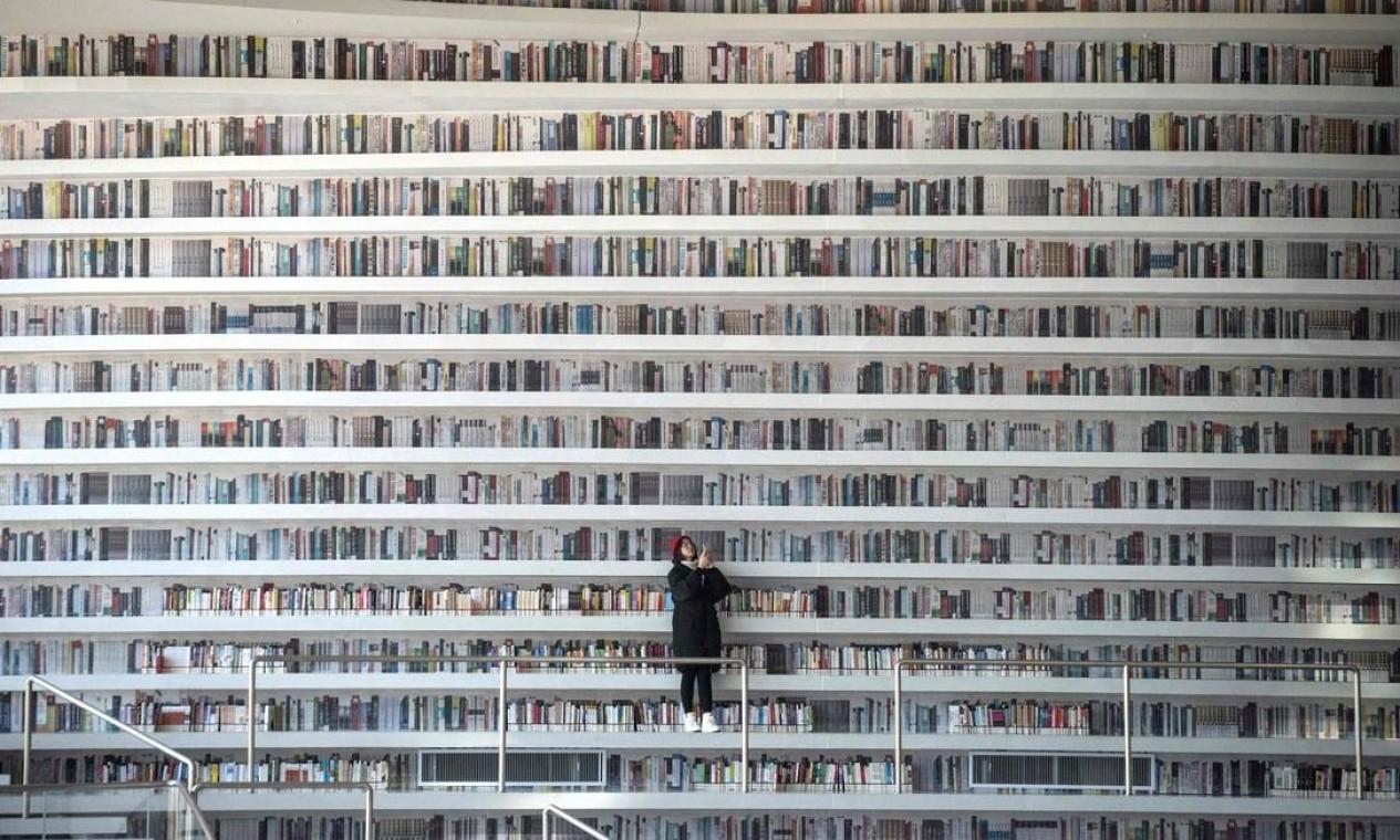 Mas os visitante que pretendiam pegar livros nas prateleiras mais altas ficam na vontade.'Há uma grande diferença entre as fotografias e a realidade', diz Jiang Xue, estudante de medicina de 21 anos, ao lado de uma estante dedicada ao Partido Comunista no poder na China. Foto: FRED DUFOUR / AFP