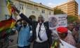 Festa em Harare. 'Mugabe, vá para casa e descanse!', diz pôster de manifestante no centro de Harare: renúncia do presidente trouxe esperança à população, mas ex-vice com histórico de massacres deve assumir o comando no Zimbábue Foto: Ben Curtis / Ben Curtis/AP
