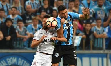 Edilson, do Grêmio, que participou do gol do jogo, disputa a bola com o argentino German Foto: NELSON ALMEIDA / AFP