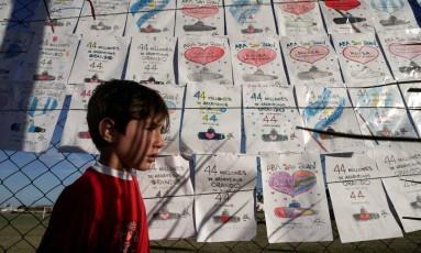 Criança em frente às mensagens de apoio deixadas na base naval de Mar del Plata, onde submarino San Juan era esperado antes do seu desaparecimento Foto: EITAN ABRAMOVICH / AFP