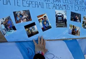 Mulher toca cartaz com fotos de um dos tripulantes do submarino desaparecido ARA San Juan, na base de Mar del Plata, na Argentina Foto: Esteban Felix / AP
