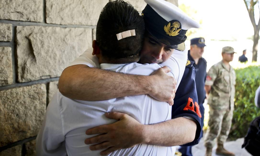 Oficiais da Marinha Argentina se abraçam na Base Naval de Mar del Plata, após anúncio de que uma provável explosão causou o desaparecimento do submarino Foto: Esteban Felix / AP