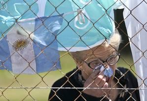 Um mulher chora em frente a grade da Base Naval de Mar del Plata, onde bandeiras foram penduradas em homenagem aos 44 tripulantes do ARA San Juan; as buscas continuam até que se tenha certeza do que causou o desaparecimento Foto: Esteban Felix / AP