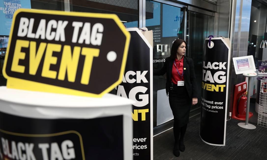 Uma funcionária se prepara para abrir as portas de uma filial da loja Currys, no distrito comercial de West End, de Londres, para a entrada dos clientes que vieram aproveitar as ofertas da Black Friday Foto: SIMON DAWSON / REUTERS