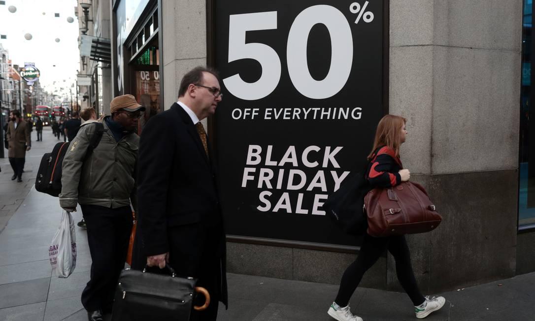 Pedestres atravessam um sinal em frente a uma loja da Miss Selfridge, na Oxford Street, em Londres, onde um cartaz anuncia descontos de 50% Foto: SIMON DAWSON / REUTERS